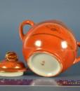Antiek porseleinen oranje melkkan en suikerpot